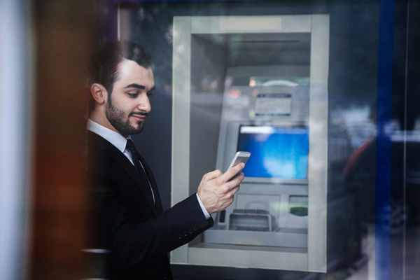 Picture of a man by an ATM.